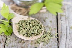 Portion of dried Lovage. (detailed close-up shot) with fresh leaves on wood Stock Photo