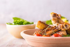 Portion of few chicken legs on plate in front of  potatoes and green salad Stock Images
