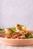 Portion of few chicken legs on plate in front of  potatoes and salad Royalty Free Stock Image
