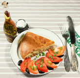 Portion of fish pie with slices of tomatoes on white plate. Royalty Free Stock Photography