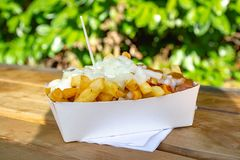Portion of fresh fried Belgium potatoes sticks with inion, ketshup and sate sauce. Served outside royalty free stock images
