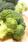 Portion of fresh green broccoli on wooden cutting board Stock Images