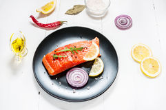 Portion of fresh salmon fillet with aromatic herbs, spices and v Royalty Free Stock Image