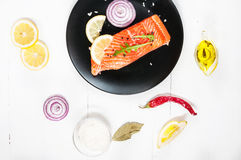 Portion of fresh salmon fillet with aromatic herbs, spices and v Royalty Free Stock Images