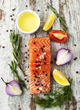 Portion of fresh salmon fillet. With aromatic herbs, spices and vegetables Royalty Free Stock Photos