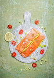 Portion of fresh salmon fillet with lemon and cooking ingredients on round gutting board, top view. Healthy food Stock Photography