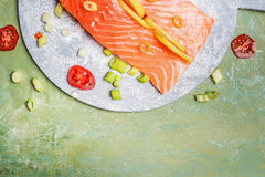 Portion of fresh salmon fillet with lemon and cooking ingredients on rustic background, top view, border. Healthy food or diet eating concept Stock Photo