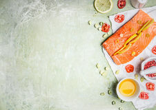 Portion of fresh salmon fillet with lemon slices, oil and ingredients for cooking on light wooden background, top view, place for. Text. Healthy food or diet Royalty Free Stock Photography