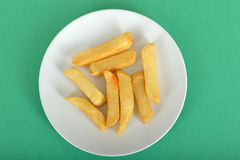 Portion of Fried Chips. Portion of potato chips on a plate against a green background Stock Photography
