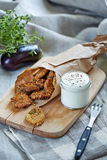 A portion of fried eggplant served with souce. A portion of fried eggplant served in folding parchment bag with souce in the jar Stock Photo