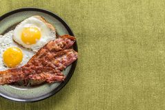 Portion of fried eggs with bacon Stock Images