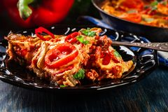 Portion of frittata with eggs, sausage chorizo, red pepper, green pepper, tomatoes, cheese and chili in a plate on wooden table. Stock Photos