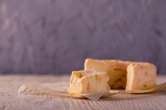 Portion of golden camembert on white wooden board Stock Image