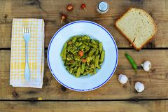 Plate of green beans. Portion of green beans, bread slices and garlic on the table Royalty Free Stock Photo