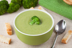 Portion of green broccoli cream soup restaraunt. Recipe with croutons on textile background stock image