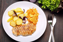 Portion of grilled chicken, baked potatoes and carrots salad Stock Image