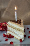 Portion homemade cream cake with candle and pomegranate seeds and chocolate spread Stock Photo