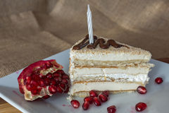Portion homemade cream cake with candle and pomegranate seeds and chocolate spread Royalty Free Stock Images
