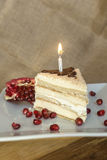 Portion homemade cream cake with candle and pomegranate seeds and chocolate spread Royalty Free Stock Photos