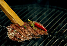 Portion of hot spicy beef steak grilling on a BBQ. Garnished with a whole red cayenne chili pepper and fresh rosemary in a close up view with copy space Stock Images