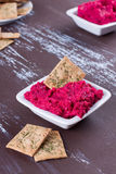 Portion of hummus. Portion of beetroot hummus with crackers royalty free stock image