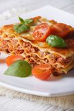 Portion of Italian lasagna on a white plate. Vertical Stock Photos