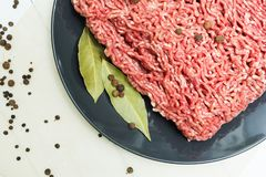 Portion of juicy fresh minced meat on a black plate on a wooden table with pepper and bay leaf. Top view royalty free stock image