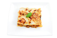 Portion of lasagna. Plate portion of lasagna with meat with basil leaf trimmed and isolated Stock Image
