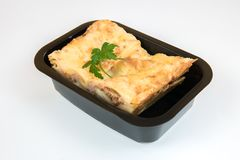 Portion of lasagne. Decorated with a piece of fresh parsley in a black take-out package Stock Images