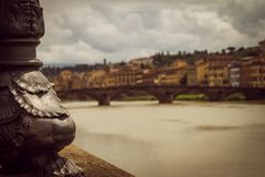 Portion of a luminaire next to the river. Panoramic view of the city of Florence unfocused. royalty free stock photo