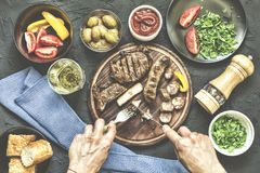 Portion lunch. A la carte lunch. Fresh vegetables, a barbecue steak and various snacks.Man eats a juicy barbecue steak royalty free stock photo