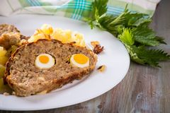 Portion of meatloaf on white plate with mashed potatoes and fresh nettle Royalty Free Stock Photos