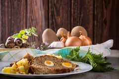 Portion of meatloaf on white plate with potatoes and fresh nettle Stock Images