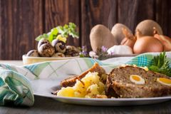 Portion of meatloaf on white plate with potatoes and quail eggs Royalty Free Stock Photos