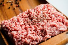 Portion of Minced Meat on an old wooden table closeup shot. Fresh raw meat minced on a wooden tray. spices, salt and onions. cooking food Copy space, top view Royalty Free Stock Photos