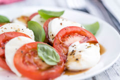 Portion of Mozarella with Tomatoes and Balsamico dressing. (selective focus; close-up shot royalty free stock image