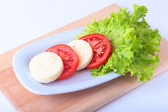 Portion of Mozzarella with Tomatoes, lettuce leaf and Balsamic dressing on white plate. selective focus close-up shot. Portion of Mozzarella with Tomatoes Stock Images