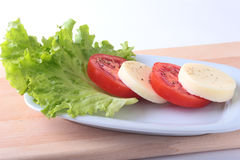 Portion of Mozzarella with Tomatoes, lettuce leaf and Balsamic dressing on white plate. selective focus close-up shot. Portion of Mozzarella with Tomatoes Royalty Free Stock Images