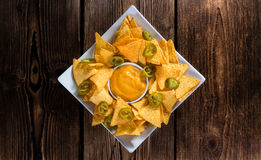 Portion of Nachos (with Cheese Dip). On an old wooden table stock images