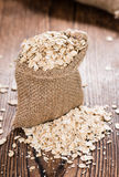 Portion of Oatmeal. On dark wooden background (close-up shot stock photography