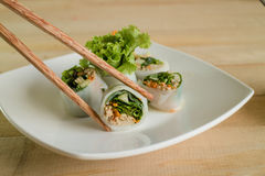 Portion off fresh spring rolls,vegetable and pork on white plate wood table. Stock Photo
