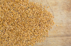 Portion of organic golden flaxseed spilled on a cutting board Royalty Free Stock Photos