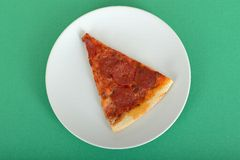 Portion of Pizza. Pepperoni Pizza on a plate against a green background Royalty Free Stock Image