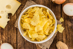 Portion of Potato Chips Cheese and Onoion taste on wooden back. Cheese and Onion Potato Chips on rustic wooden background close-up shot stock photos