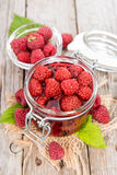 Portion of preserved Raspberries. Preserved Raspberries in a glass with some fresh fruits Stock Images