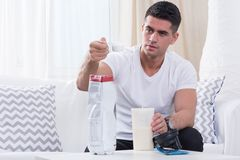 Portion of proteins before workout. Athletic man sitting on a sofa preparing protein drink stock photos