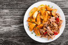 Portion of pulled slow-cooked meat with fried potato wedges royalty free stock photos