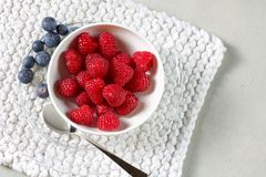Portion of raspberries in a white cup with some blueberries. And cotton place mat Stock Images