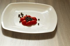 A portion of the rdl pepper and sweet peas lie on a white plate. A portion of the red bell pepper and sweet peas lie on a white plate stock image