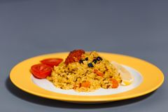 A portion of ready-made pilaf of raw and African rice with slices of carrots and barberry stock images
